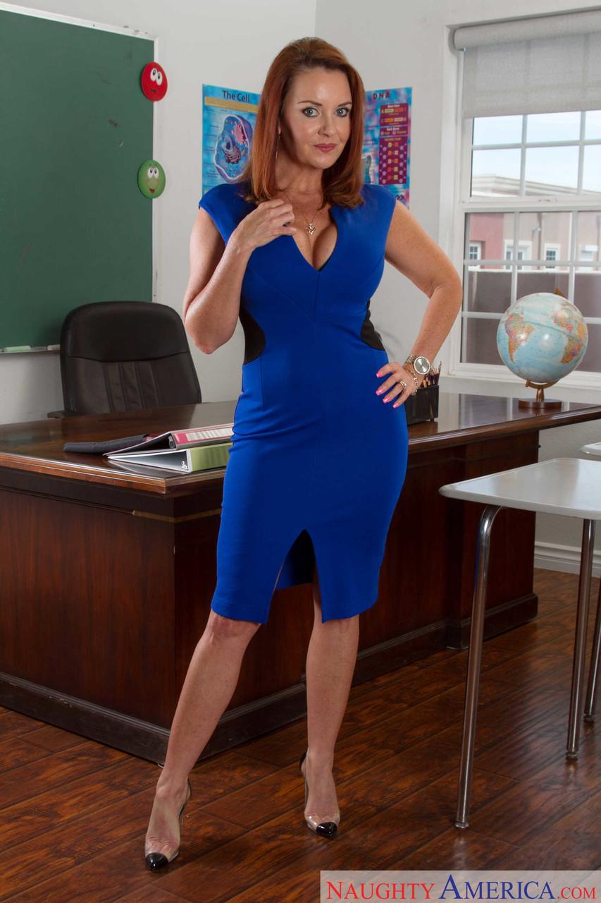 Mature redhead Janet Mason does classroom strip to expose big tits & curvy ass